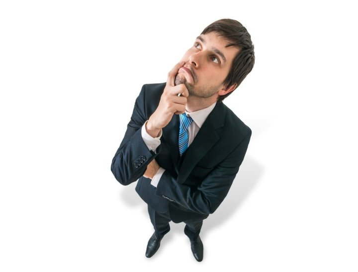 Young thoughtful businessman is thinking. View from top. Isolated on white background.