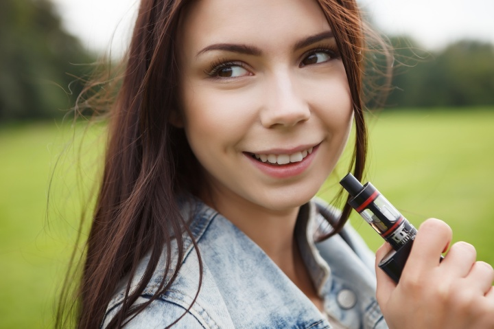 Young girl vaping e-cig device
