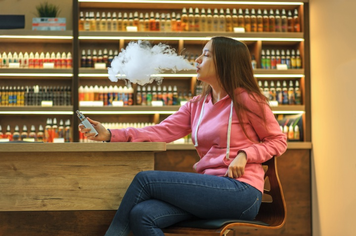 Vape woman. Portrait of young cute girl in pink hoodie smoking an electronic cigarette in the bar.