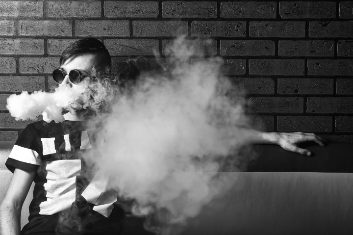 Vape. Young handsome white guy in sunglasses is admiting puffs of steam from the electronic cigarette. Vaping. Teenager. Black and white photo.